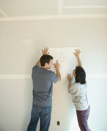 Couple looking at blueprints inside construction site