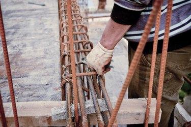 builder workers installing metal rods bars into framework reinfo