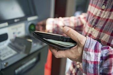 Man withdrawing money from ATM with focus on wallet