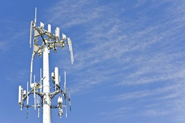 Cell phone telecommunication tower with wispy clouds, blue sky.