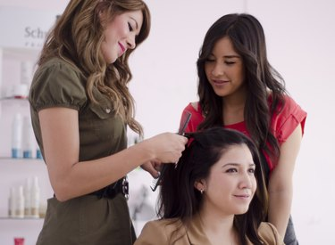 Cute girl learning from an experienced hairstylist
