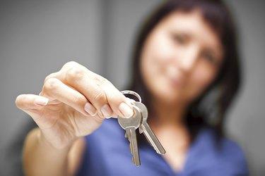 Realtor in empty apartment giving keys