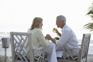 Mature couple holding hands sitting at restaurant on beach