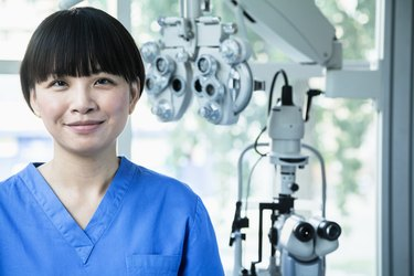 Portrait of smiling female optometrist with eye test equipment