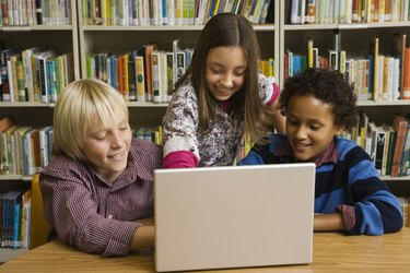 Children in library with laptop computer