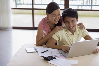Smiling couple with paperwork and laptop