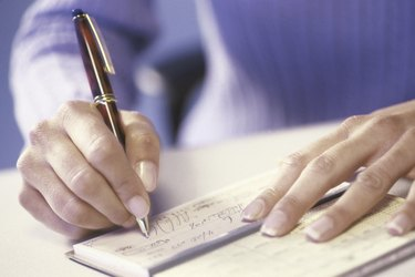 Close-up of a person writing a check