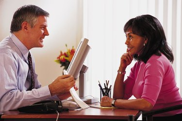 Man behind desk showing document to woman