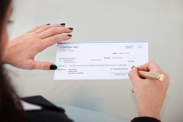 Businesswoman Signing Cheque