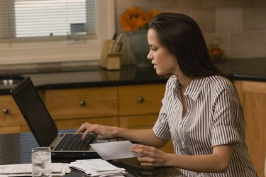 Woman with a laptop computer and bills