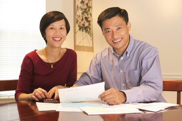 Portrait of a couple smiling at the viewer while sitting at the table going over their finances and bills