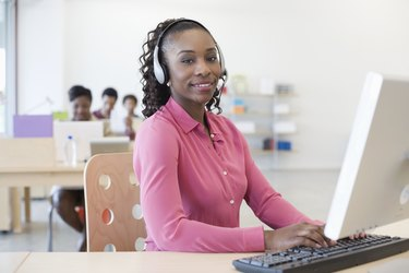 Young business woman in office using computer, wearing headphones, smiling, others in background