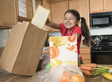 Hispanic girl unpacking groceries in kitchen