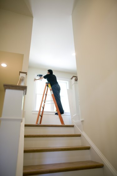 Man on ladder, fixing windows in home