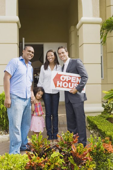 Hispanic real estate agent and African family in front of house
