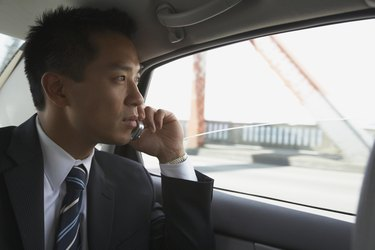 Asian businessman using cell phone in backseat of car