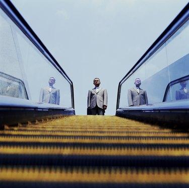 Businessman Looking Down Escalator