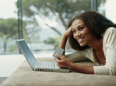 Young woman lying on bed with holding credit card and laptop, smiling, side view