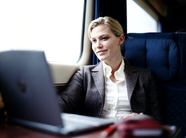 Businesswoman using laptop on train, smiling (focus on woman)