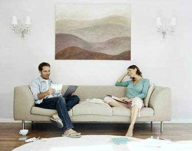 Couple Sits on Sofa Examing Their Bills