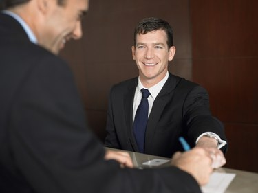 Businessman Signing a Document at a Reception Desk
