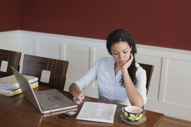 Woman Working on Laptop Computer, Calculator and Tax Documents at Dining Room Table
