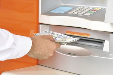 Hand taking money from ATM