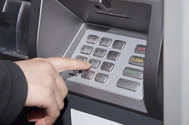 Woman pressing number button on ATM machine