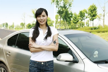 Young woman holding car keys in front of car