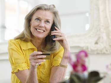 Mature Woman Using Credit Card And Phone