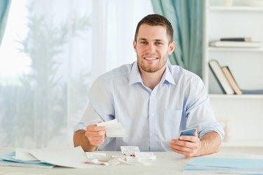 Businessman with pocket calculator checking bills