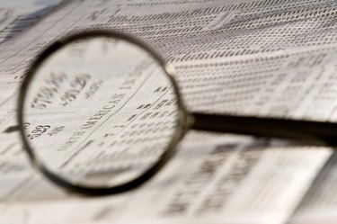 Magnifying glass highlighting investment stock quotes in business section of newspaper.