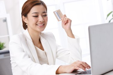 Young business lady holding credit card in front of laptop