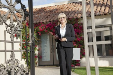 Portrait of a senior real estate agent walking with clipboard in front of house