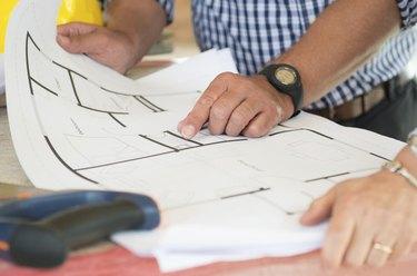 Architect Showing Plan On Blueprint