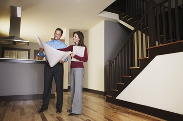 Man and woman looking at blueprint of house