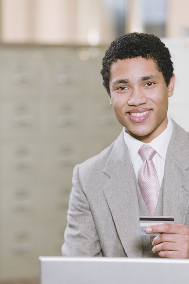Mixed race businessman with laptop holding credit card