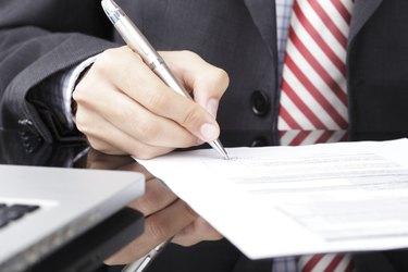 Businessman writing on a form