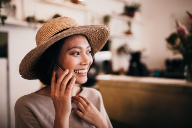 Woman wearing straw hat talking on mobile phone