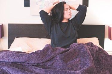 Woman in sweatshirt waking up in bed