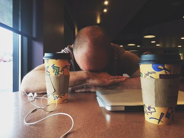Man with his head down in front of two cups of coffee