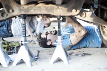 Young men working underneath cars