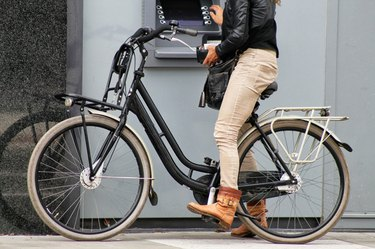 Hipster on a bike using an ATM