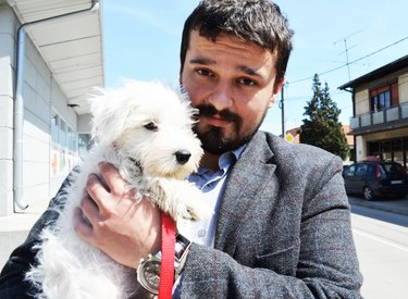Man in business suit holding small white dog