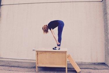 Women bending over while standing atop a desk