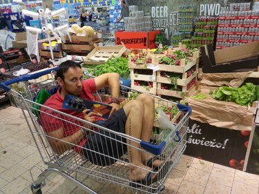 Man sitting in grocery cart in produce aisle