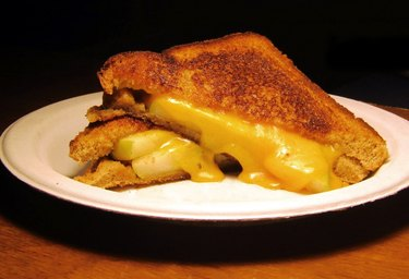 A white plate with a sandwich cut in half, filled with apples and cheddar cheese oozing down onto the plate.