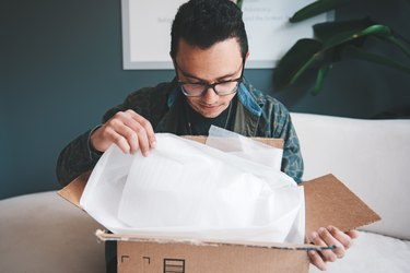 Man opening cardbox box with tissue paper inside