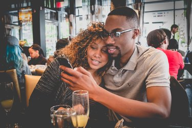 Young Black couple at restaurant looking at phone, cuddling
