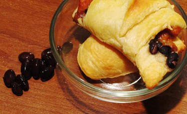 Baked crescent roll stuffed with black beans, chicken, cheese, and salsa, in the background there are scattered black beans.